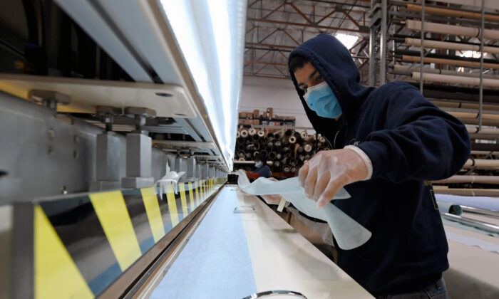 Johnny Diaz makes surgical masks out of spunbond polypropylene fabric using an impulse welder at Polar Shades Sun Control in Las Vegas, Nevada. (Ethan Miller/Getty Images)