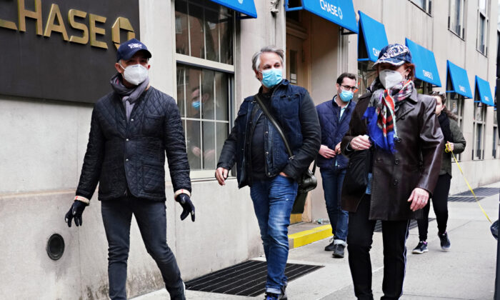 A group of people wear protective masks during the CCP virus pandemic in New York City on April 19, 2020. (Cindy Ord/Getty Images)