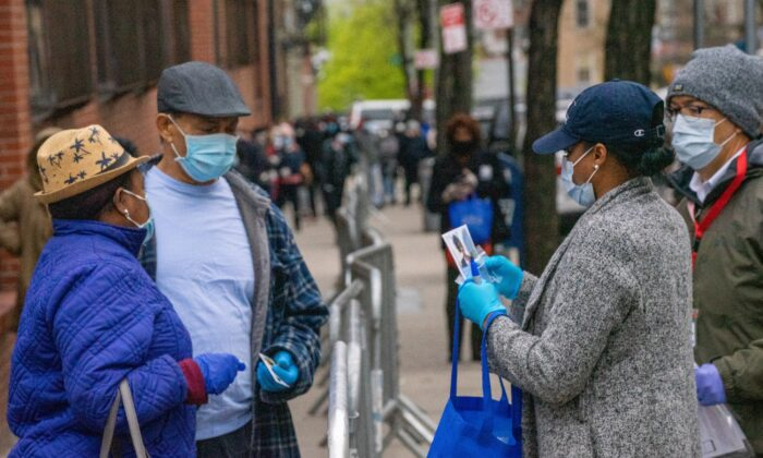 People stand in line for COVID-19 testing at NYC Health + Hospitals/Gotham Health, Morrisania in the Bronx borough of New York City on April 20, 2020. (David Dee Delgado/Getty Images)