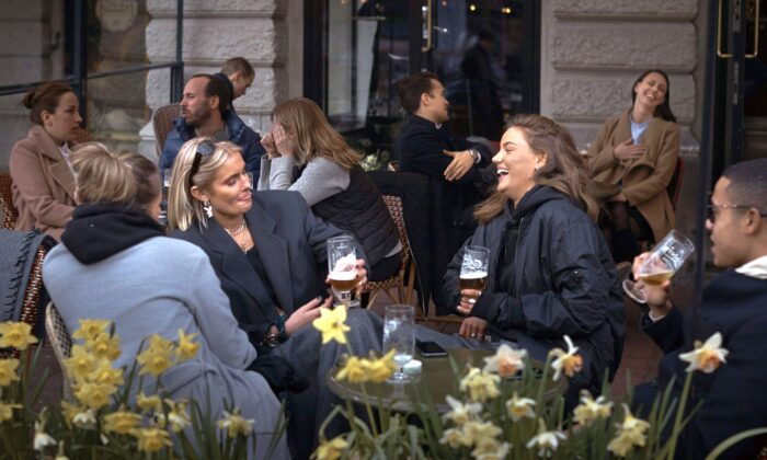 People socialize at a pub in Stockholm, Sweden, on April 8, 2020. Swedish authorities have advised the public to practice social distancing due to the pandemic, but still allow a large amount of personal freedom. (Andres Kudacki/AP Photo)