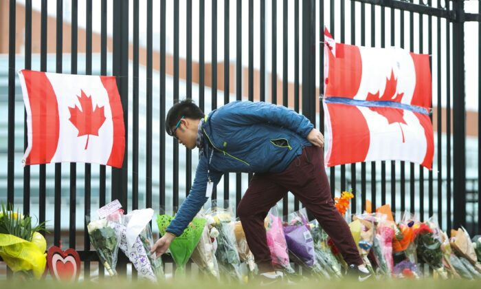 A person leaves flowers at a make-shift memorial dedicated to Constable Heidi Stevenson at RCMP headquarters in Dartmouth, Nova Scotia, on April 20, 2020. (The Canadian Press/Riley Smith)
