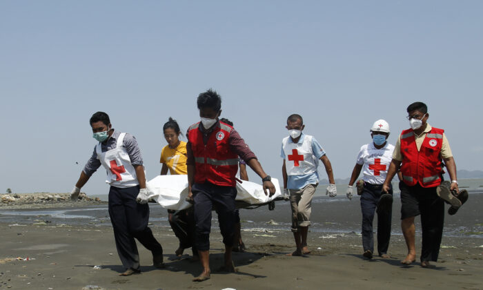 Members of the Myanmar Red Cross carry a dead body of a driver from a boat in Sittwe, Rakhine State, killed while delivering test kits for the CCP virus, in Burma, on April 21, 2020. (STR / AFP via Getty Images)