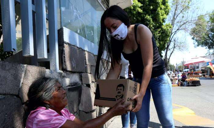 """An employee of the clothing brand """"El Chapo 701,"""" owned by Alejandrina Gisselle Guzman, daughter of the convicted drug kingpin Joaquin """"El Chapo"""" Guzman, hands out a box with food, face masks and hand sanitizers to an elderly woman as part of a campaign to help cash-strapped elderly people during the COVID-19 disease outbreak, in Guadalajara, Mexico, April 16, 2020.  (Fernando Carranza/Reuters File)"""
