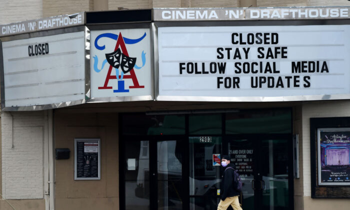 A man wearing a face mask to protect himself from the coronavirus walks past a closed theater in Arlington, Virginia on April 18, 2020. ( Olivier Douliery/AFP via Getty Images)