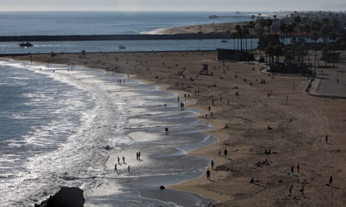 People are seen along Corona del Mar State Beach in Newport Beach, Calif., on April 15, 2020. Southern California has seen warmer weather over the last few days as social distance guidelines due to COVID-19 are still in place. (Michael Heiman/Getty Images)