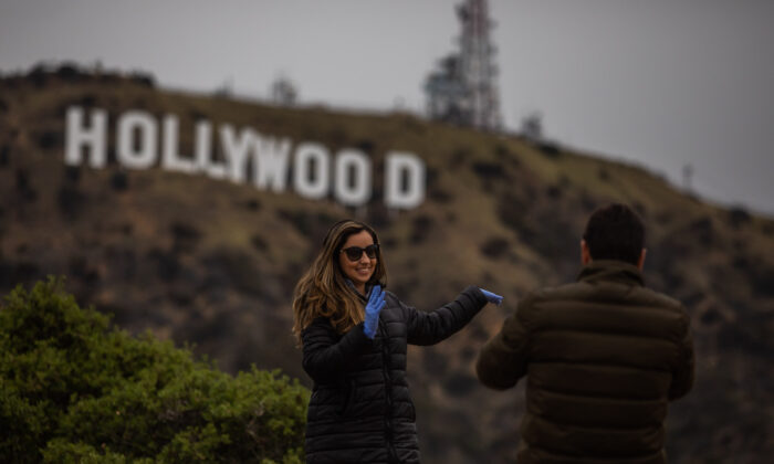 A woman poses below the Hollywood sign in Hollywood, Calif., on March 22, 2020. (Apu Gomes/AFP via Getty Images)
