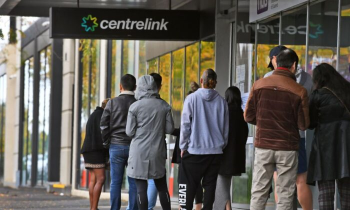 People queue up outside a Centrelink office for government payments in Melbourne on April 20, 2020. (William West/AFP via Getty Images )