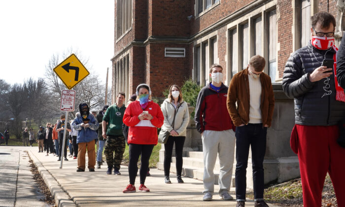 Voters wait in line to enter a polling place at Riverside University High School in Milwaukee, Wis., on April 07, 2020. (Scott Olson/Getty Images)