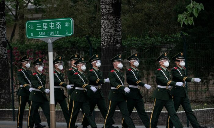: Chinese police officers wear protective masks as they march during a shift change on April 14, 2020 in Beijing. (Kevin Frayer/Getty Images)