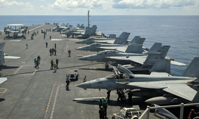 US Navy F/A-18 Super Hornets multirole fighters and an EA-18G Growler electronic warfare aircraft (2nd R) on board USS Ronald Reagan (CVN-76) aircraft carrier as it sails in South China Sea on its way to Singapore, on Oct.16, 2019. (Catherine Lai/AFP via Getty Images)