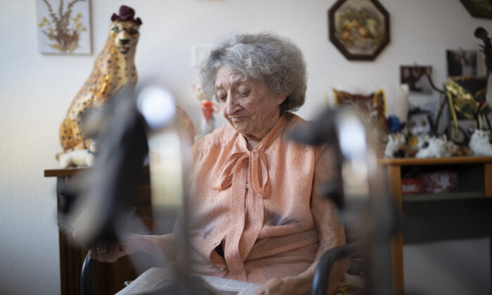 Marie Louise Kopp looks at a newspaper as she waits for a call from her son in her room at a nursing home in Ammerschwir, France on April 16, 2020. (Jean-Francois Badias/AP)