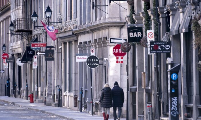 A couple walks along a deserted street in Old Montreal on March 31, 2020, amid the ongoing global pandemic. (The Canadian Press/Paul Chiasson)
