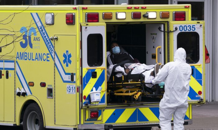 Paramedics transfer a patient to Verdun Hospital in Montreal on April 21, 2020. (The Canadian Press/Paul Chiasson)