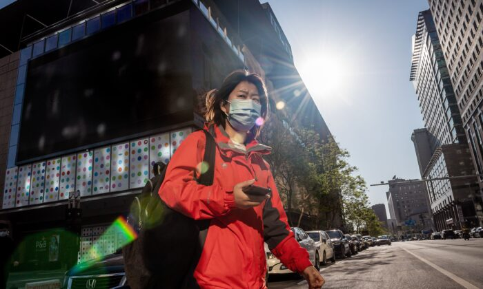 A woman wearing a face mask amid concerns over the CCP virus crosses a street in Beijing on April 22, 2020. (Nicolas Asfouri/AFP via Getty Images)