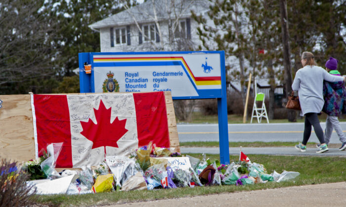 A woman comforts her daughter after they placed flowers at an impromptu memorial in front of the RCMP detachment in Enfield, Nova Scotia, Canada, on April 20, 2020. (Tim Krochak/Getty Images)