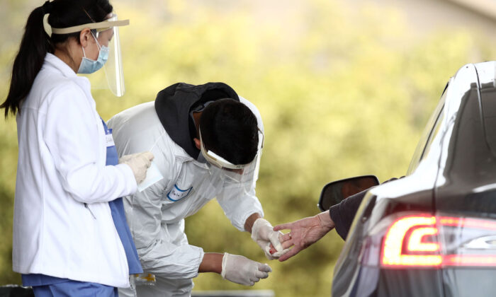 A medical professional administers a coronavirus test at a drive-thru testing location at the Bolinas Fire Department in Bolinas, Calif., on April 20, 2020.  (Ezra Shaw/Getty Images)