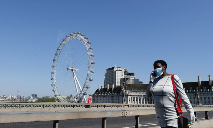 A woman wearing a mask to protect against the CCP virus walks over Westminster Bridge in London, on April 22, 2020. (Frank Augstein/AP)