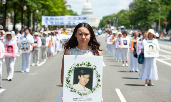 A woman holds a photo of a man killed by the Chinese regime's persecution of Falun Gong, during a parade in Washington on July 17, 2014. (Larry Dye/The Epoch Times)