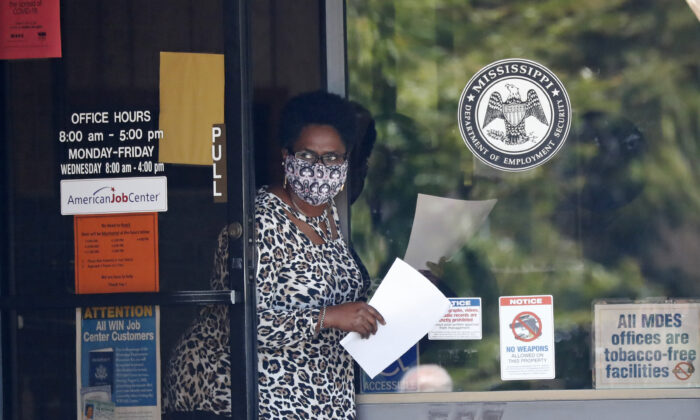 A masked worker at this state WIN job center holds an unemployment benefit application form as she waits for a client in Pearl, Miss., on April 21, 2020. (Rogelio V. Solis/AP Photo)