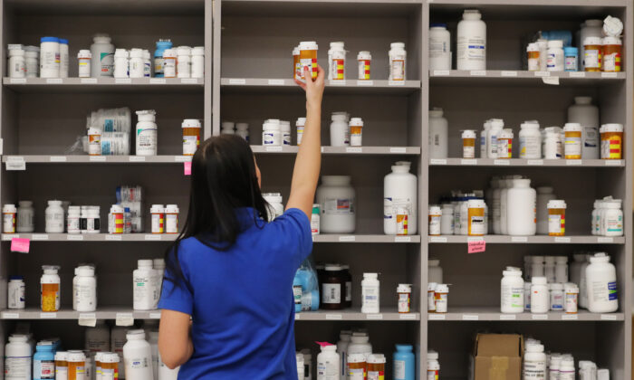 A pharmacy technician grabs a bottle of drugs off a shelve at the central pharmacy of Intermountain Heathcare in Midvale, Utah, on Sept. 10, 2018. (George Frey/Getty Images)