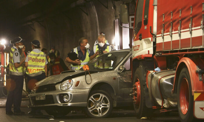 Police officers and investigators inspect a vehicle involved at the crash site inside Melbourne's Burnley Tunnel on March 23, 2007 in Melbourne, Australia.  (David Caird-Pool/Getty Images)