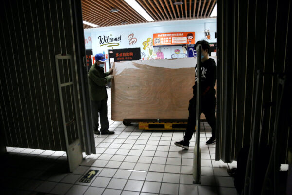 orkers wearing face masks move wood planks from a clothing store after it went out of business following the coronavirus disease (COVID-19) outbreak, in Beijing