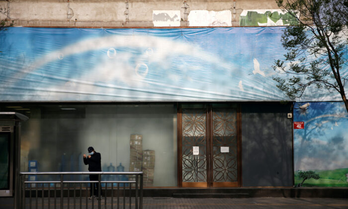 A man wearing a face mask is seen in front of a closed shop on a street, following an outbreak of the COVID-19, in Beijing, China, on April 16, 2020. (Tingshu Wang/Reuters)