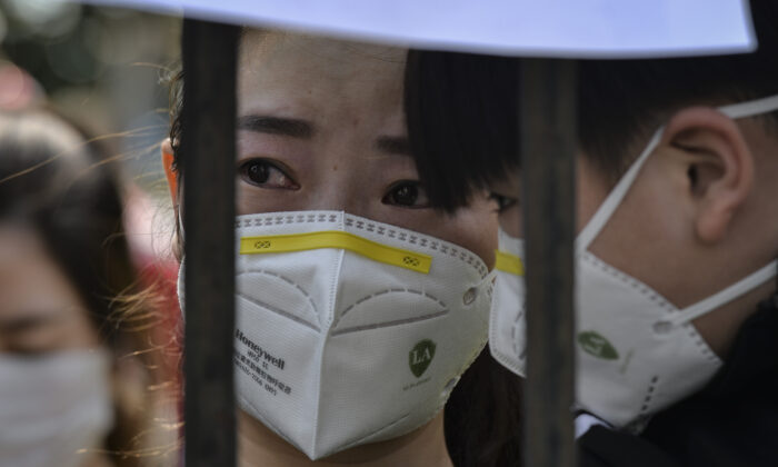 A Wuhan resident reacts as a medical assistance team from Yunnan province depart after helping with the COVID-19 coronavirus recovery effort in Wuhan, China, on March 18, 2020. (AFP via Getty Images)