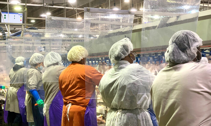Tyson Foods employees are seen wearing protective masks and standing between plastic dividers at the company's poultry processing plant in Camilla, Ga., in a file photo. (Tyson Foods via AP)
