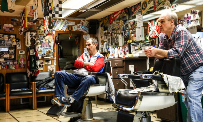 Barbers and brothers Tommy (L) and Jimmy Checkler watch the latest news on the coronavirus in their empty barbershop in the City of Worthington in Columbus, Ohio, on March 17, 2020. (Charlotte Cuthbertson/The Epoch Times)