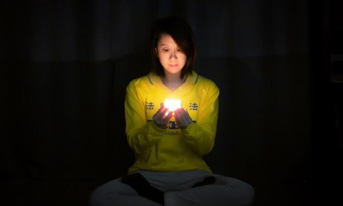 A woman in New York participates in the online candle vigil to commemorate the persecution of Falun Gong practitioners in China, on April 23, 2020. (Courtesy of Tuidang Center)