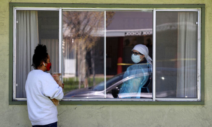 A visitor talks with a nurse through a window at the Gateway Care and Rehabilitation Center in Hayward, Calif., on April 14, 2020. (Justin Sullivan/Getty Images)