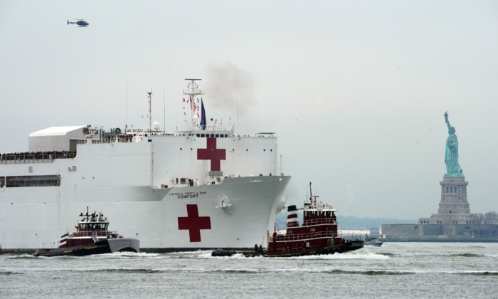 The USNS Comfort medical ship moves up the Hudson River past the Statue of Liberty as it arrives in New York on March 30, 2020. (Bryan Smith/AFP via Getty Images)