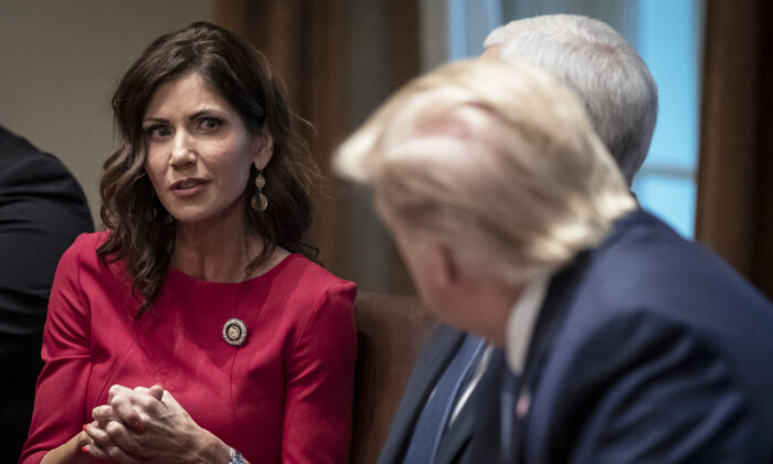 (L-R) Governor of South Dakota Kristi Noem speaks as President Donald Trump listens during a meeting about the Governors Initiative on Regulatory Innovation in the Cabinet Room of the White House in Washington on Dec. 16, 2019. (Drew Angerer/Getty Images)