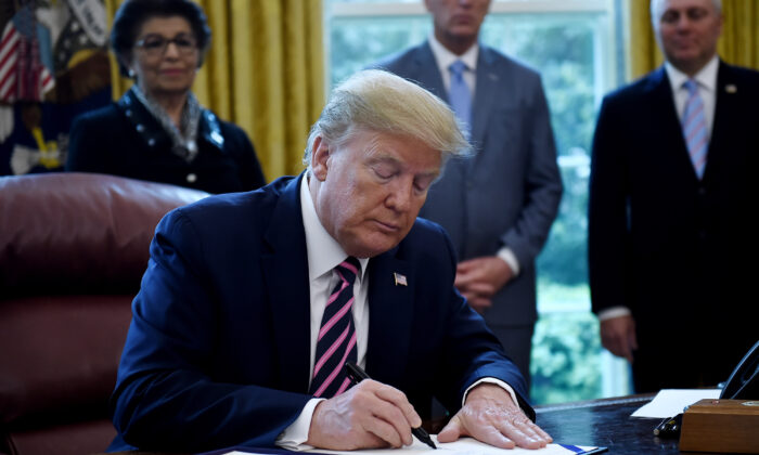 President Donald Trump signs the Paycheck Protection Program and Health Care Enhancement Act in the Oval Office of the White House in Washington, on April 24, 2020. (Olivier Douliery/AFP via Getty Images)