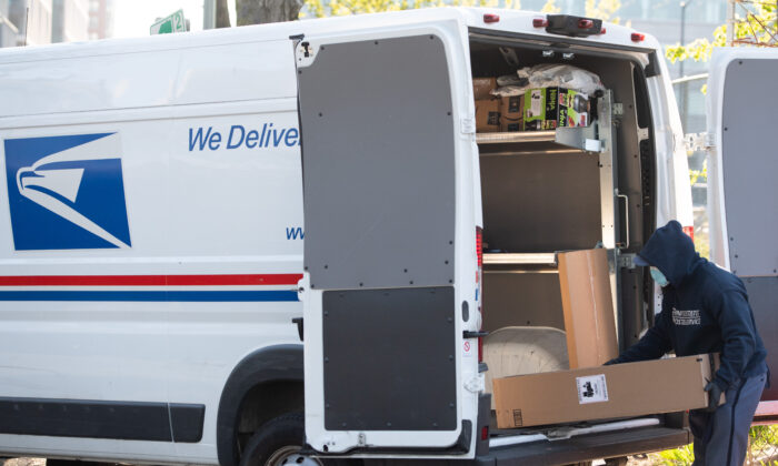 A mailman wearing a mask and gloves to protect himself and others from COVID-19, loads a postal truck with packages at a United States Postal Service (USPS) post office location in Washington, on April 16, 2020. (Saul Loeb/AFP via Getty Images)