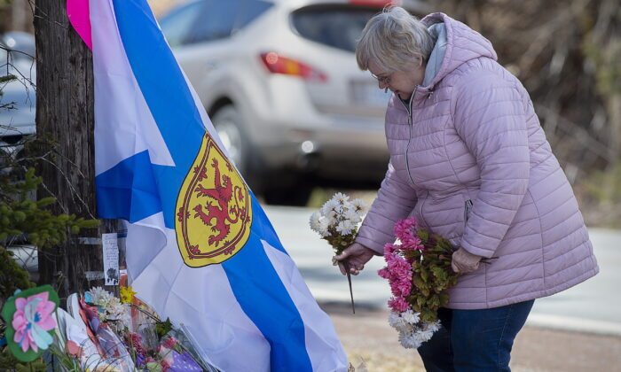 A woman pays her respects to victims of a mass shooting at a roadside memorial in Portapique, Nova Scotia, Canada, on April 23, 2020. (Andrew Vaughan/The Canadian Press via AP)