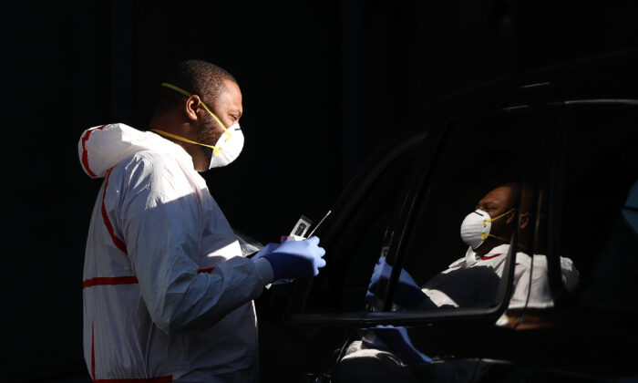 Joseph Little, a nurse, takes samples from people to test them for the CCP virus at a drive-through station outside the AllCare Family Medical Clinic in Washington on April 6, 2020. (Samira Bouaou/The Epoch Times)