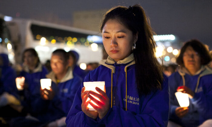 Falun Dafa practitioners hold a candlelight vigil as a peaceful protest near the Chinese Consulate in New York on April 25, 2014, to mark the anniversary of the April 24, 1999 large-scale peaceful protest in Beijing. (Samira Bouaou/Epoch Times)