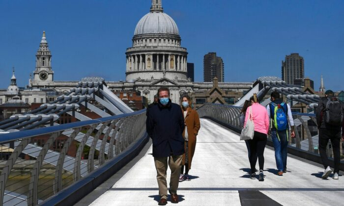 A man walks on Millennium Bridge wearing a protective mask, in London, on April 25, 2020. (Alberto Pezzali/AP Photo)