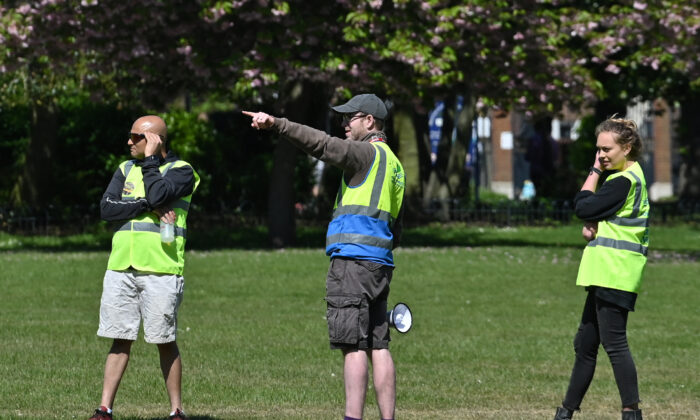 Workers wearing a Tower Hamlets Borough Council hi-vis jackets gesture as they stand in Victoria Park, east London on April 25, 2020, during the national lockdown due to the COVID-19 pandemic. (Justin Tallis/AFP via Getty Images)