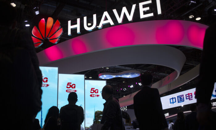 Attendees walk past a display for 5G services from Chinese technology firm Huawei at the PT Expo in Beijing, in this undated photo. (Mark Schiefelbein/AP Photo)