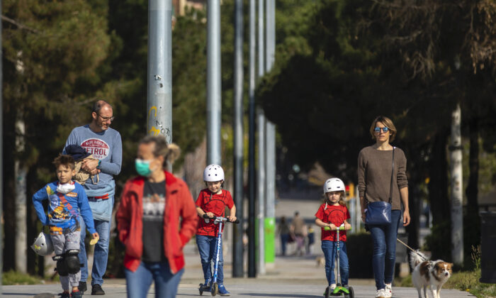 Families with their children walk along a boulevard in Barcelona, Spain, on April 26, 2020. (Emilio Morenatti/AP Photo)
