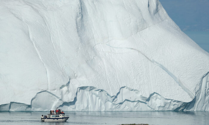 A boat carrying tourists motors past an iceberg at the mouth of the Ilulissat Icefjord during unseasonably warm weather near Ilulissat, Greenland on July 30, 2019. (Sean Gallup/Getty Images)