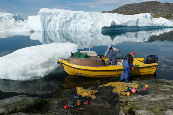 Inuit fishermen prepare a net as free-floating ice floats behind at the mouth of the Ilulissat Icefjord during unseasonably warm weather on July 30, 2019 near Ilulissat, Greenland. (Sean Gallup/Getty Images)