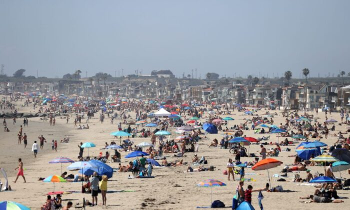 People are seen gathering on the beach north of the pier in Newport Beach, Calif., on April 25, 2020. (Michael Heiman/Getty Images)