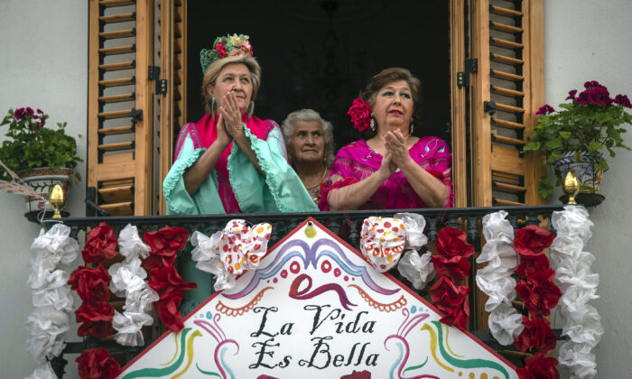 Women in traditional dress, applaud from their decorated balcony during the annual traditional April Fair in Seville, Spain on April 25, 2020. (Miguel Morenatti/AP Photo)