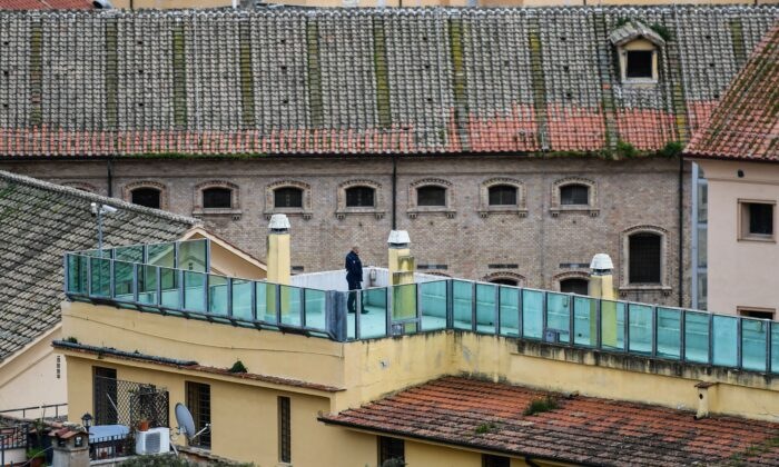 A prison guard patrols a prison building's terrace overlooking the Regina Coeli prison in central Rome on March 9, 2020. (ALBERTO PIZZOLI/AFP via Getty Images)