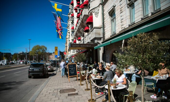 People have lunch at a restaurant in Stockholm, Sweden, on April 22, 2020, during the COVID-19 pandemic. (Jonathan Nackstrand/AFP via Getty Images)