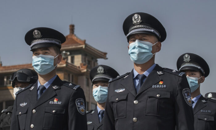 Chinese police officers wear protective masks at the Beijing Railway Station on April 4, 2020. (Kevin Frayer/Getty Images)
